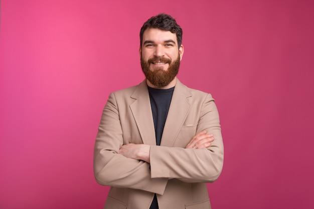 Homem barbudo confiante com os braços cruzados está sorrindo na parede rosa