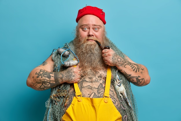 Homem barbudo confiante olha seriamente para a câmera fuma cachimbo e posa com rede de pesca tem tatuagens usa chapéu vermelho com anzóis gosta de passatempo favorito