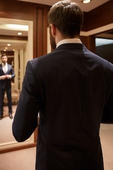 Homem barbudo corrigindo seu terno contra o espelho