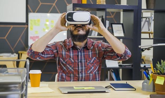 Homem barbudo criativo usa óculos de realidade virtual em sua mesa no escritório