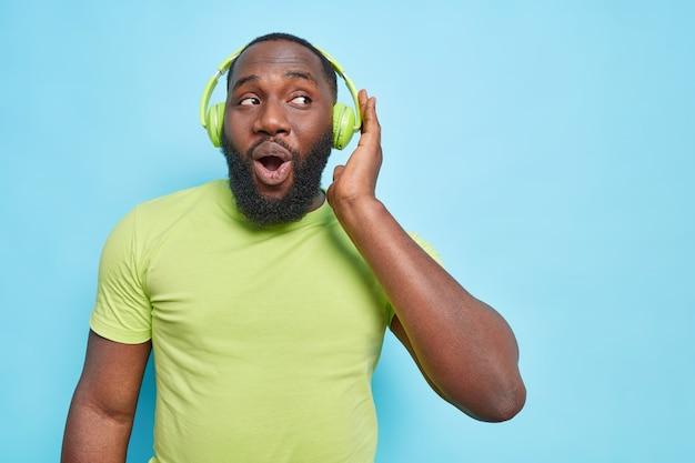 Homem barbudo curioso e surpreso mantém a mão nos fones de ouvido e a boca aberta, vestido com uma camiseta verde, ouvindo música favorita isolada sobre a parede azul