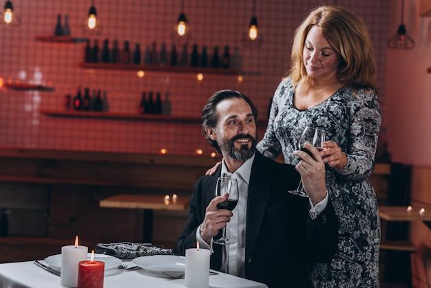 Homem barbudo dá um copo de vinho tinto para uma mulher em pé próximo
