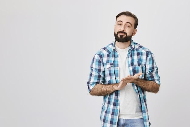 Homem barbudo de aparência séria esfrega as mãos, espera sabor ou renda