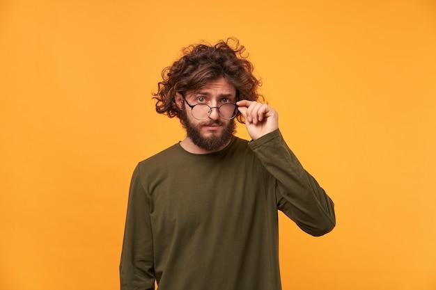 Homem barbudo de cabelos cacheados parecia curioso e tirou os óculos