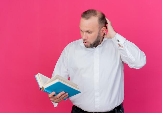 Homem barbudo de camisa branca segurando um livro aberto olhando para ele confuso em pé sobre a parede rosa