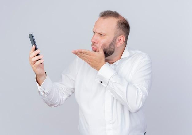 Homem barbudo de camisa branca segurando um smartphone olhando para a tela da videochamada mandando um beijo em pé sobre uma parede branca