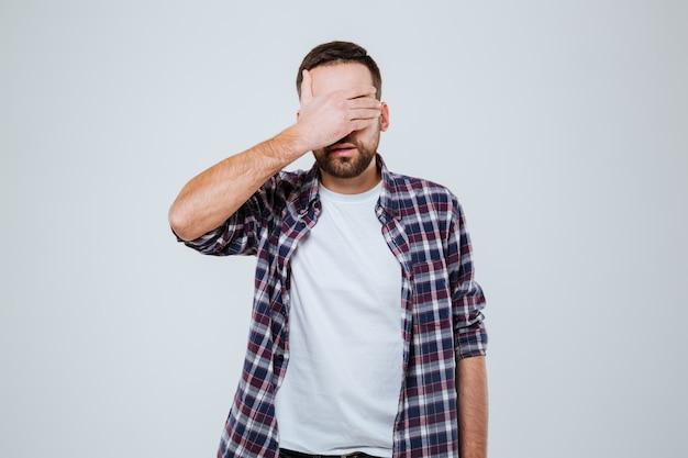 Homem barbudo de camisa cobrindo os olhos
