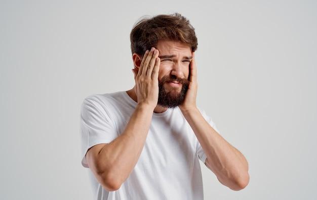Homem barbudo, de camiseta branca, segurando a cabeça, descontentamento, depressão, emoções