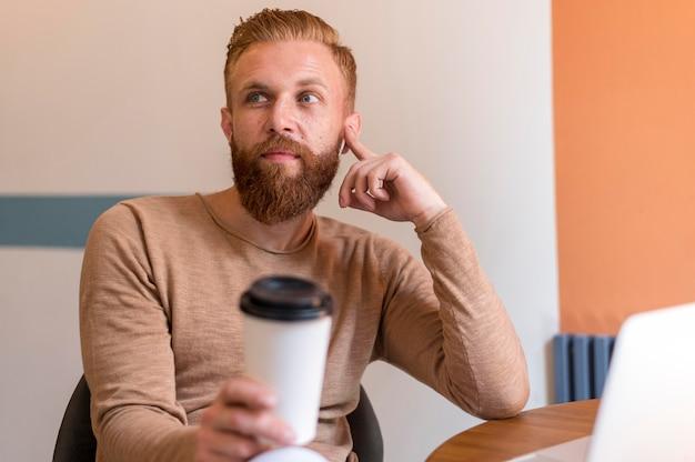 Homem barbudo de frente segurando uma xícara de café