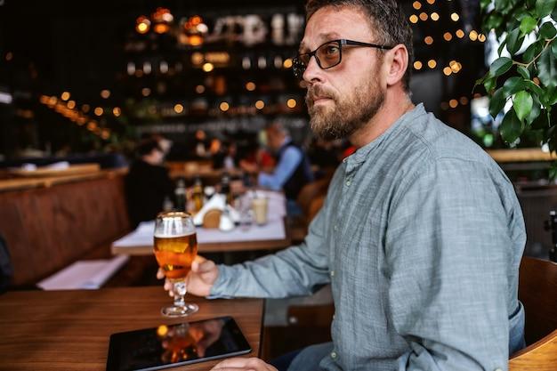 Homem barbudo de meia-idade com óculos, sentado em um bar, tomando um copo de cerveja gelada depois do trabalho