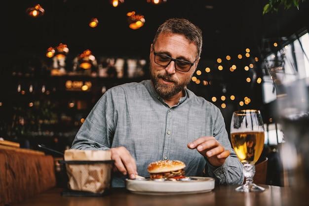Homem barbudo de meia-idade e faminto sentado em um restaurante comendo um hambúrguer delicioso