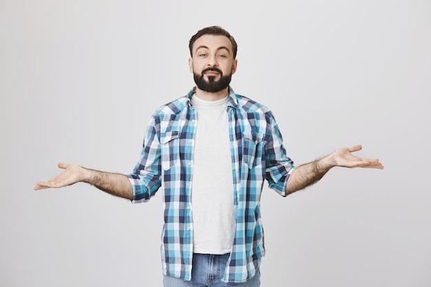 Homem barbudo de meia-idade satisfeito apresentando duas variantes, estendendo as mãos para os lados