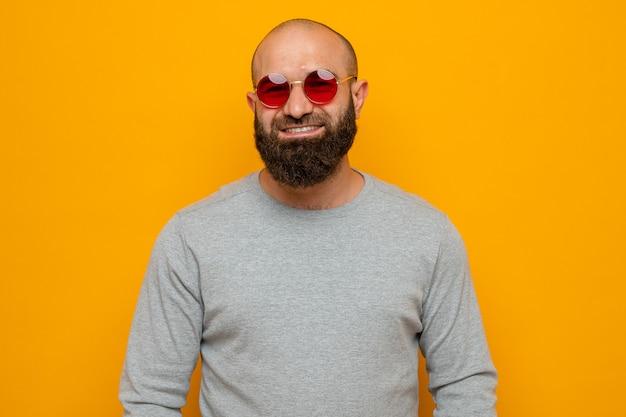 Homem barbudo de moletom cinza com óculos vermelhos, olhando para a câmera, feliz e positivo, sorrindo amplamente em pé sobre um fundo laranja