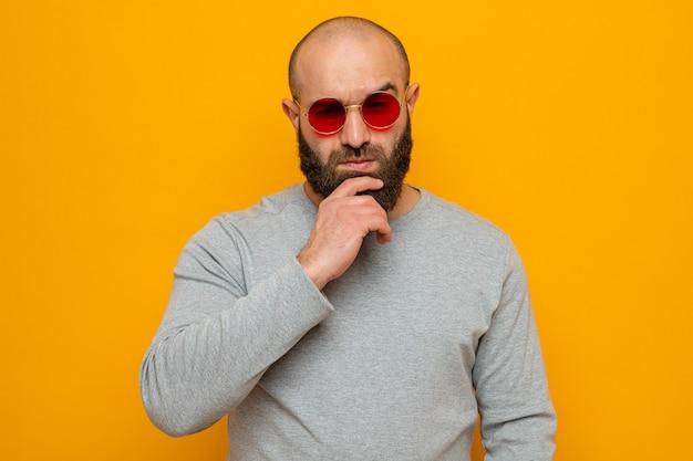 Homem barbudo de moletom cinza com óculos vermelhos olhando para o lado com a mão no queixo com expressão pensativa pensando em pé sobre um fundo laranja