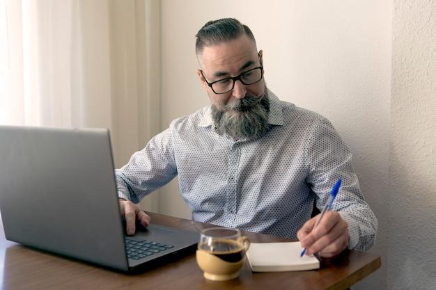 Homem barbudo de óculos e um café tomando notas no bloco de notas enquanto trabalhava no laptop no escritório em casa para a mesa