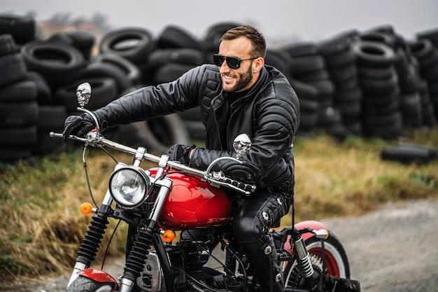 Homem barbudo de óculos escuros e jaqueta de couro, sorrindo enquanto está sentado em uma motocicleta vermelha na estrada.