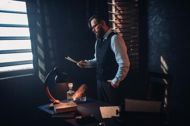 Homem barbudo de óculos lendo texto manuscrito