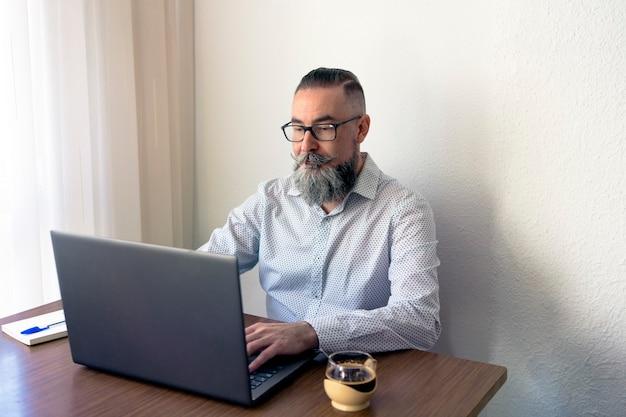 Homem barbudo de óculos tomando café e um bloco de notas na mesa trabalhando no laptop no escritório em casa