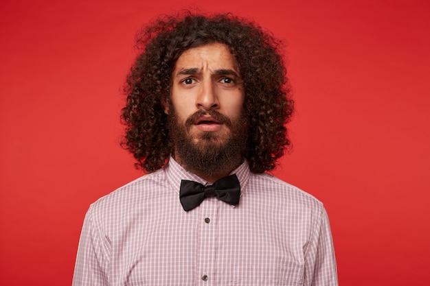 Homem barbudo, de olhos castanhos e confuso, com cabelo encaracolado escuro posando sobre um fundo vermelho em roupas elegantes, sobrancelhas franzidas e parecendo perplexo com a câmera
