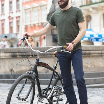 Homem barbudo de pé com sua bicicleta na cidade
