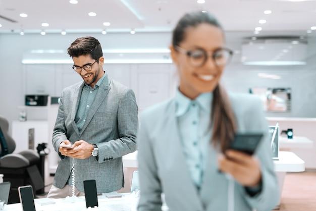 Homem barbudo de raça mista sorridente com roupa formal, experimentando o telefone inteligente na loja de tecnologia. em primeiro plano mulher segurando o telefone inteligente. foco seletivo no homem.