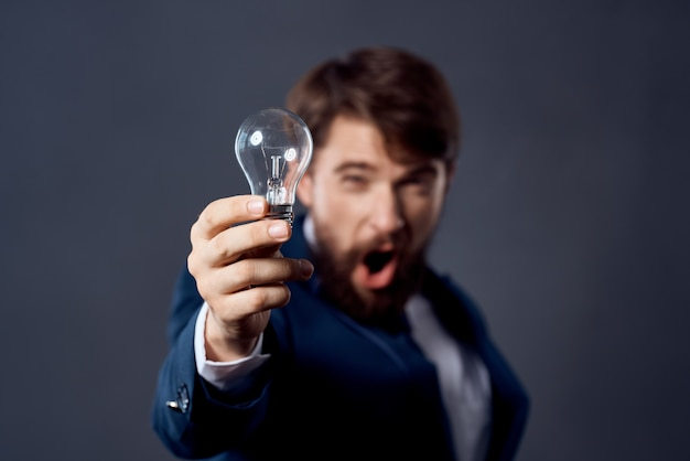 Homem barbudo de terno com uma lâmpada nas mãos, uma ideia brilhante de inovação