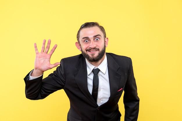 Homem barbudo de terno fazendo gesto de despedida