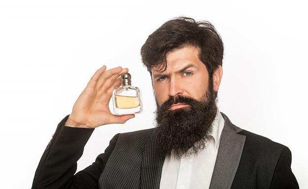 Homem barbudo de terno segurando um frasco de perfume