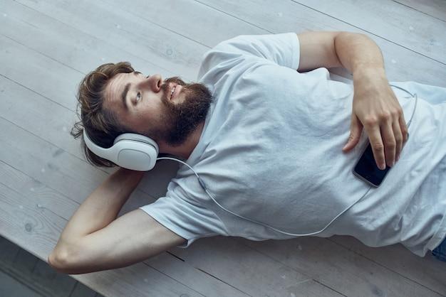 Homem barbudo deitado no parapeito da janela com fones de ouvido divertidos