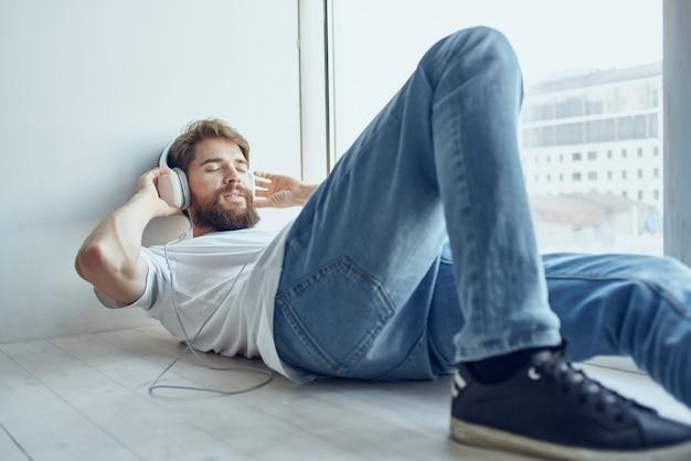 Homem barbudo deitado perto da janela usando fones de ouvido.