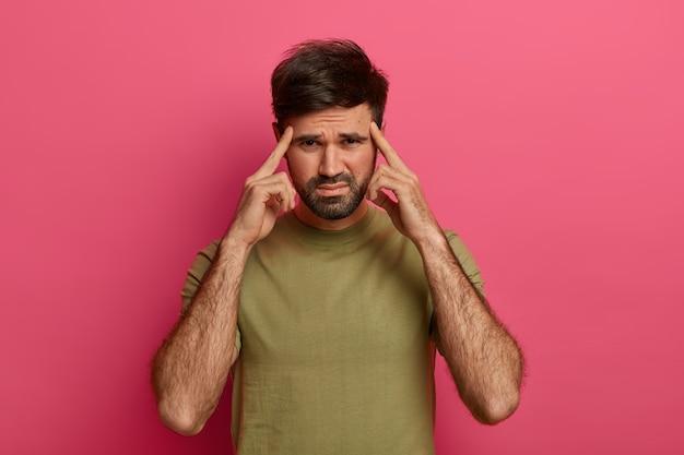 Homem barbudo deprimido e frustrado franze a testa e mantém os dedos indicadores nas têmporas