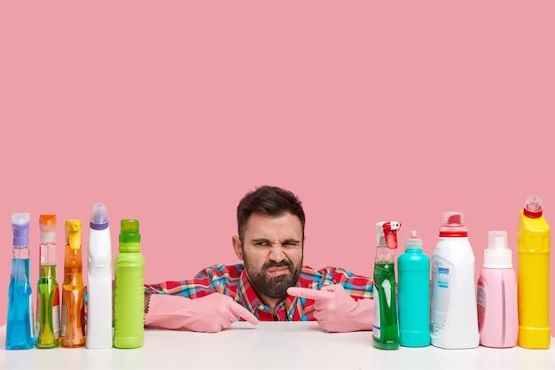 Homem barbudo descontente franze a testa em descontentamento, aponta para produtos de limpeza, usa luvas, senta-se à mesa