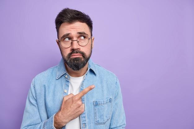 Homem barbudo descontente franze os lábios não gosta de algo amuado expressão do rosto desapontado usa óculos camisa jeans