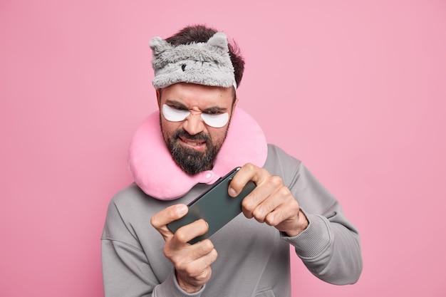 Homem barbudo descontente sério focado em smartphone joga videogame online enquanto viaja de longa distância no transporte usa venda nos olhos na testa, travesseiro de viagem ao redor do pescoço, tapa-olhos