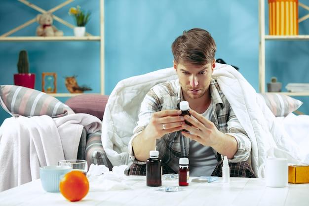 Homem barbudo doente com gripe sentado no sofá em casa coberto com um cobertor quente e bebendo xarope da tosse. a doença, a gripe, o conceito de dor. relaxamento em casa. conceitos de saúde.