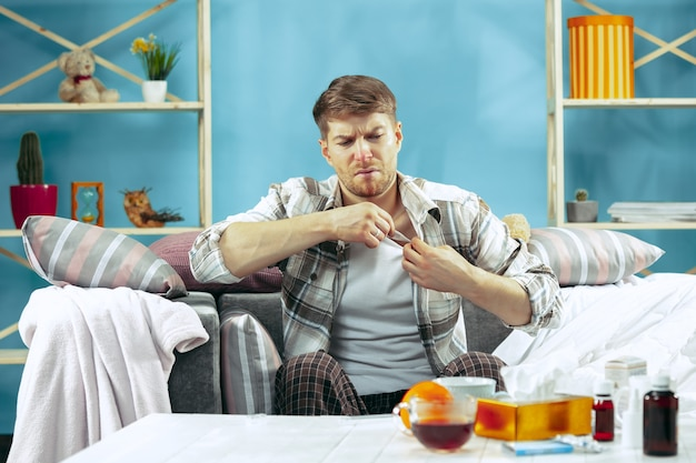 Homem barbudo doente com gripe sentado no sofá em casa e medindo a temperatura corporal. o inverno, doença, gripe, conceito de dor. relaxamento em casa. conceitos de saúde.