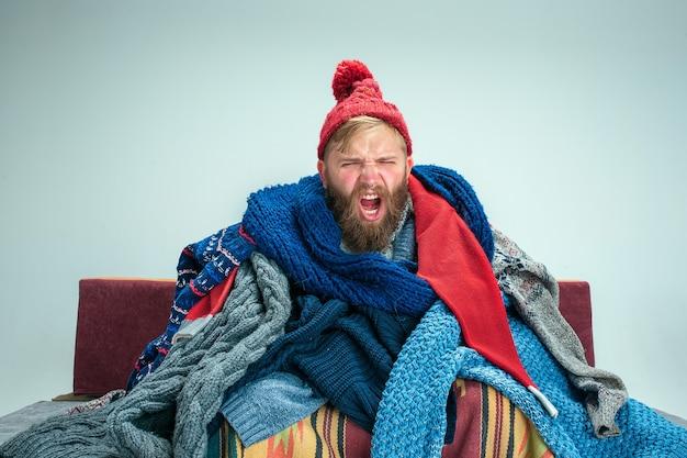 Homem barbudo doente com gripe sentado no sofá em casa ou estúdio coberto com roupas quentes de malha. doença, conceito de gripe. relaxamento em casa. conceitos de saúde.