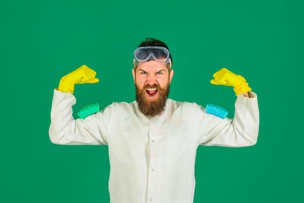 Homem barbudo, dono da casa, segura esponjas para lavar pratos, empregado doméstico com luvas e óculos de proteção