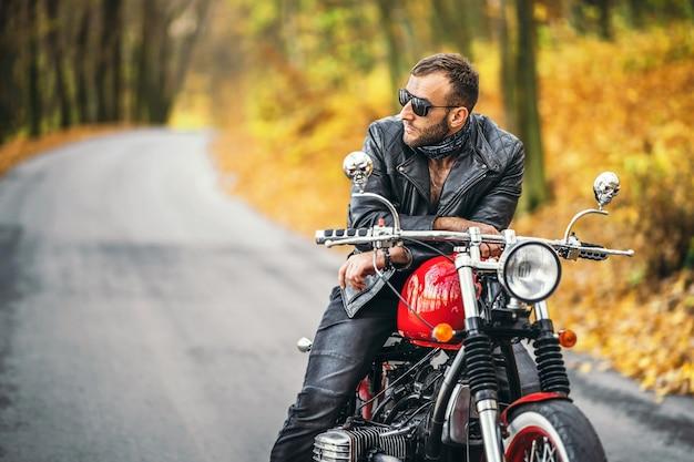 Homem barbudo e brutal de óculos escuros e jaqueta de couro, sentado em uma motocicleta na estrada na floresta