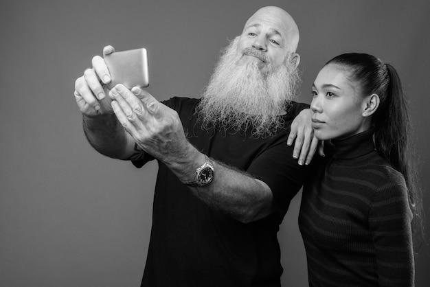 Homem barbudo e careca maduro e uma bela jovem asiática juntos contra uma parede cinza em preto e branco