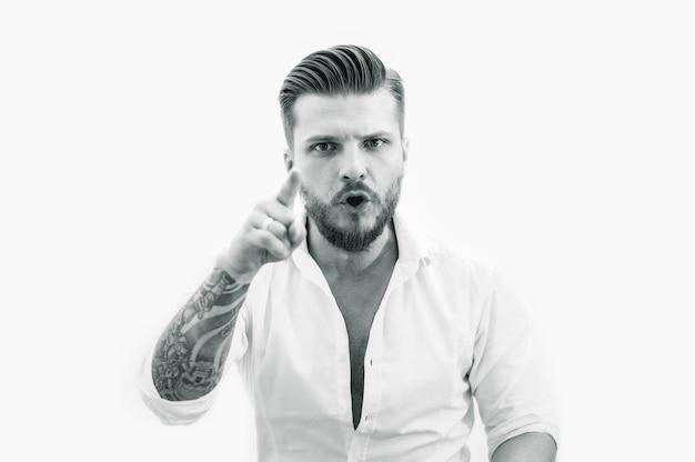 Homem barbudo e elegante mostra um dedo para a câmera. o conceito de um chefe severo. mídia mista