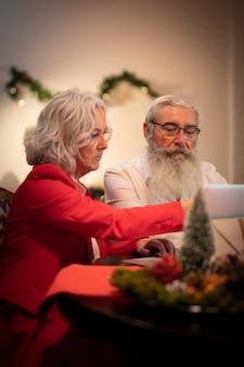 Homem barbudo e mulher comemorando o natal