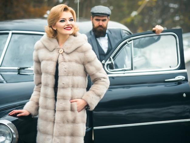 Homem barbudo e mulher sexy com casaco de pele em carro retrô. casal apaixonado em um encontro romântico. vintage.