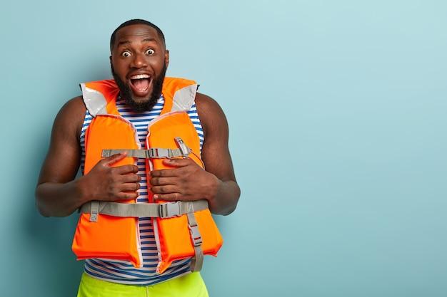 Homem barbudo e musculoso animado posando com itens de praia