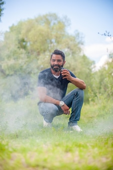 Homem barbudo elegante com cigarro eletrônico na grama. conceito de cigarro eletrônico.