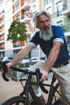 Homem barbudo elegante de cabelos grisalhos andando de bicicleta nas ruas da cidade