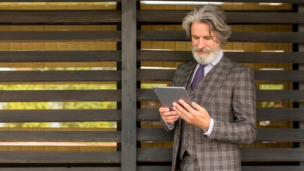 Homem barbudo elegante de frente segurando tablet Foto Premium