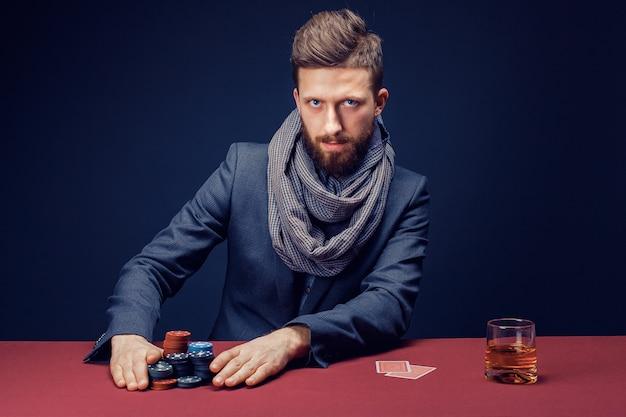 Homem barbudo elegante de terno e lenço jogando no cassino escuro