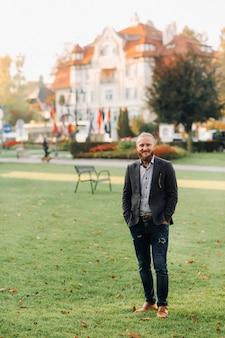 Homem barbudo elegante de terno no parque de uma cidade austríaca.