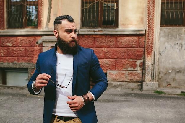 Homem barbudo elegante e descolado no fundo da cidade velha